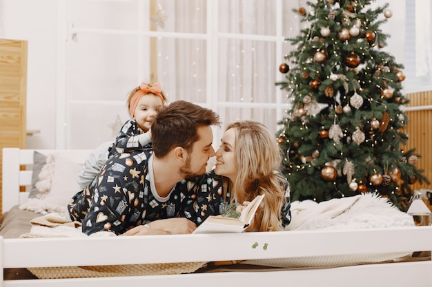 Люди ремонтируют на рождество. люди сидят на кровати. семья отдыхает в праздничном зале.