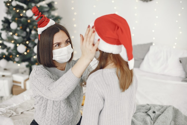 People reparing for christmas. coronavirus theme. mother playing with her daughter. child in a gray sweater.