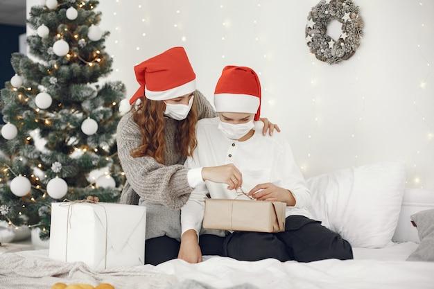 Persone che riparano per natale. tema coronavirus. madre che gioca con suo figlio. ragazzo in un maglione bianco.
