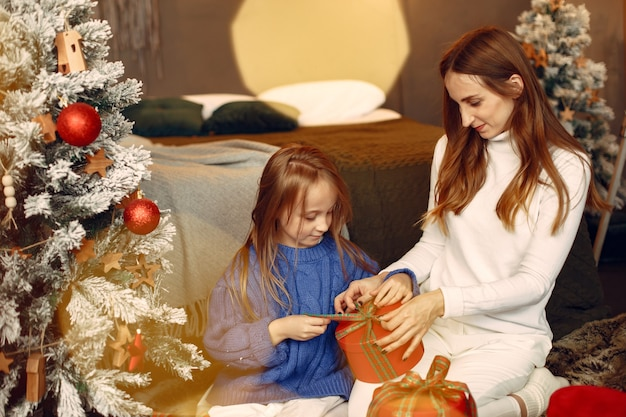 People reparing for christmas. mother playing with her daughter. family is resting in a festive room. child in a blue sweater.