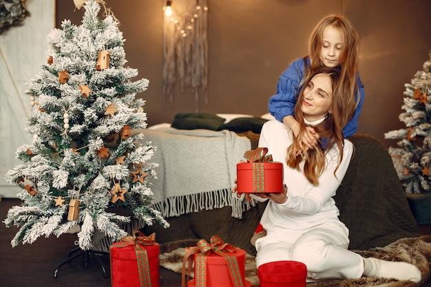 Persone che riparano per natale. madre che gioca con sua figlia. la famiglia sta riposando in una stanza festiva. bambino in un maglione blu.