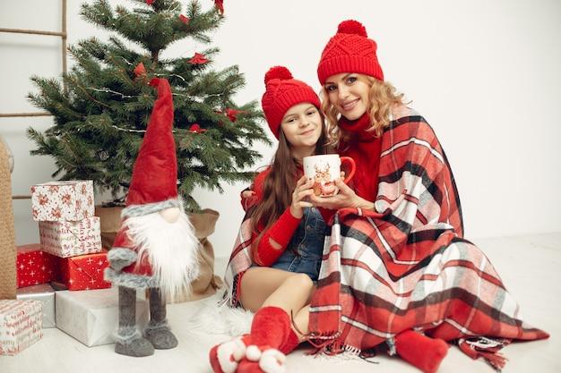 Persone che riparano per natale. madre che gioca con sua figlia. la famiglia sta riposando in una stanza festiva. bambino in un maglione rosso.