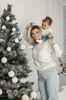 People reparing for christmas. mother playing with her daughter. family is resting in a festive room. child in a sweater sweater.