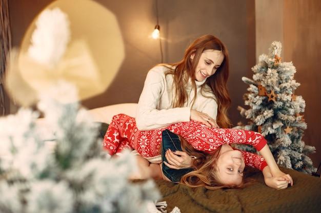 Persone che riparano per natale. madre che gioca con sua figlia. la famiglia sta riposando in una stanza festiva.