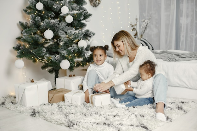 People reparing for christmas. mother playing with her daughters. family is resting in a festive room. child in a sweater sweater.