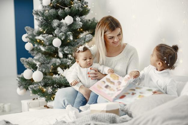 Persone che riparano per natale. madre che gioca con le sue figlie. la famiglia sta riposando in una stanza festiva. bambino in un maglione maglione.