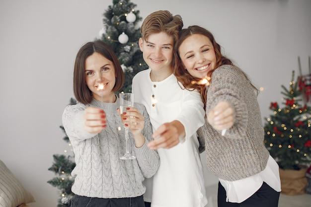 Persone che riparano per natale. madre in piedi con suo figlio. la famiglia sta riposando in una stanza festiva. persone con champagne e stelle filanti.