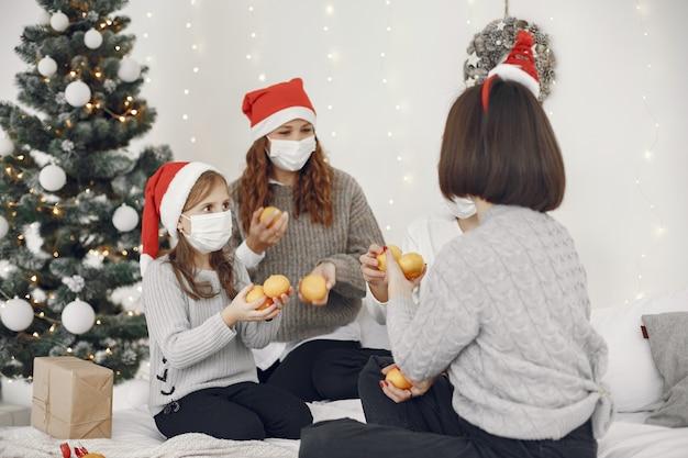 Persone che riparano per natale. due mamme che giocano con i loro figli. coronavirus thime. isolamento.