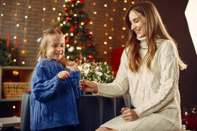 크리스마스를 돌보는 사람들. 벵골 빛을 가진 아이. 가족은 축제 방에서 쉬고 있습니다. 파란색 스웨터에 아이입니다.
