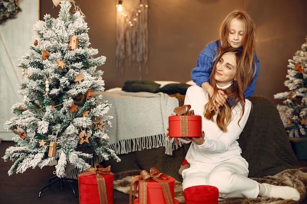 クリスマスの準備をしている人。娘と遊ぶ母。家族はお祭りの部屋で休んでいます。青いセーターを着た子供。