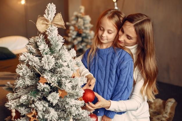 크리스마스를 돌보는 사람들. 어머니는 그녀의 딸과 함께 연주입니다. 가족은 축제 방에서 쉬고 있습니다. 파란색 스웨터에 아이입니다.