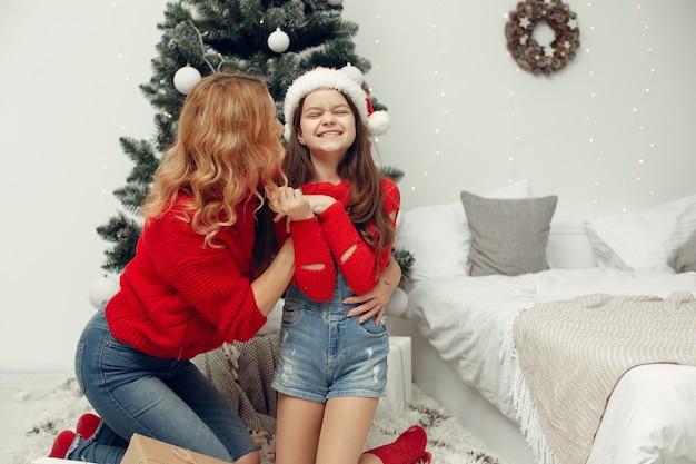 크리스마스를 돌보는 사람들. 어머니는 그녀의 딸과 함께 연주입니다. 가족은 축제 방에서 쉬고 있습니다. 빨간 스웨터에 아이.
