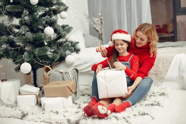 Люди делают ремонт к рождеству. мать играет со своей дочерью. семья отдыхает в праздничном зале. ребенок в красном свитере.