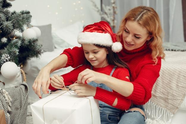 クリスマスの準備をしている人。娘と遊ぶ母。家族はお祭りの部屋で休んでいます。赤いセーターを着た子供。