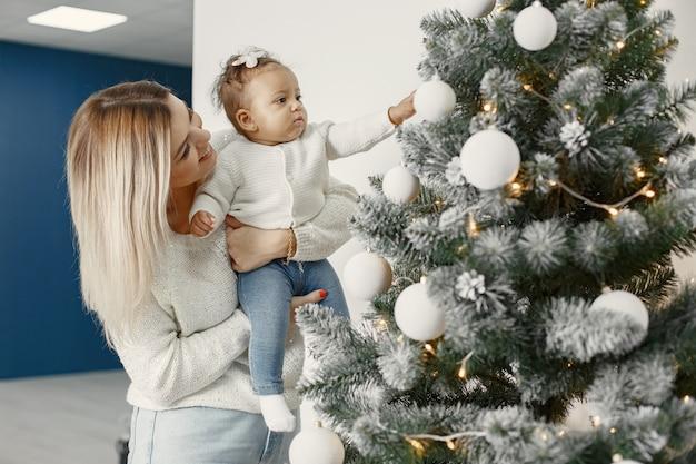 크리스마스를 돌보는 사람들. 어머니는 그녀의 딸과 함께 연주입니다. 가족은 축제 방에서 쉬고 있습니다. 스웨터 스웨터에 아이.