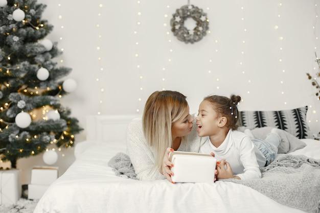 クリスマスの準備をしている人。娘と遊ぶ母。家族はお祭りの部屋で休んでいます。セーターセーターの子供。