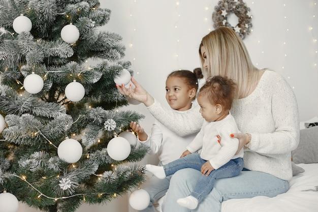 크리스마스를 돌보는 사람들. 그녀의 딸과 함께 연주 어머니입니다. 가족은 축제 방에서 쉬고 있습니다. 스웨터 스웨터에 아이.