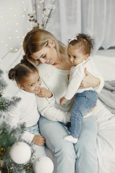クリスマスの準備をしている人。彼女の娘と遊んでいる母。家族はお祭りの部屋で休んでいます。セーターセーターの子供。