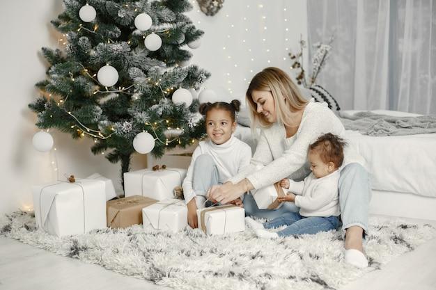 Люди делают ремонт к рождеству. мать играет со своими дочерьми. семья отдыхает в праздничном зале. ребенок в свитере-свитере.