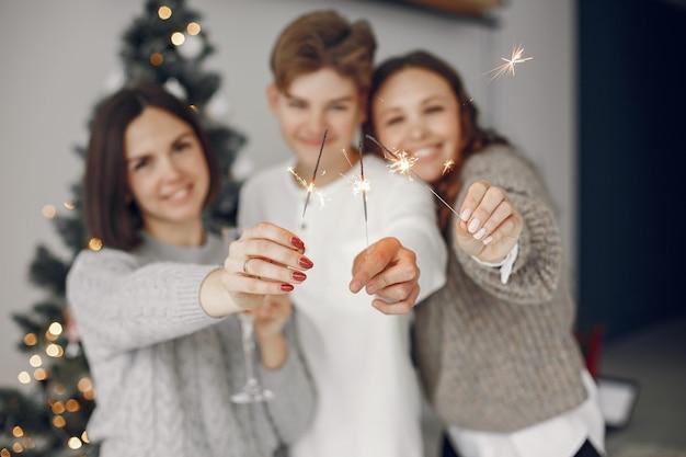 Люди делают ремонт к рождеству. мать стоя с сыном. семья отдыхает в праздничном зале. люди с шампанским и бенгальскими огнями.