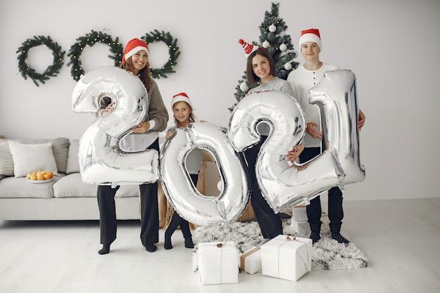 Люди делают ремонт к рождеству. люди с баллонами 2021 / семья отдыхает в праздничном зале.