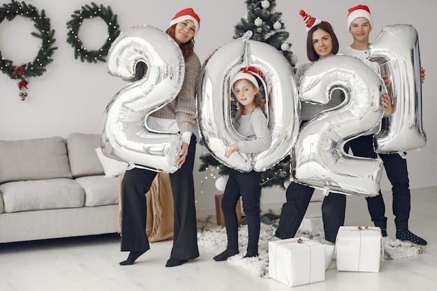 크리스마스를 돌보는 사람들. 풍선을 가진 사람들 2021 / 가족은 축제 방에서 쉬고 있습니다.