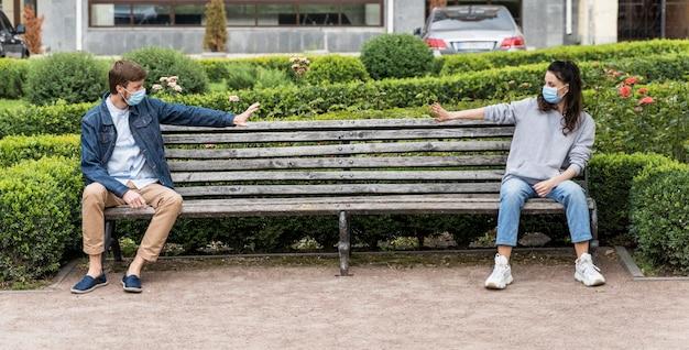 Люди, соблюдающие социальную дистанцию, сидя на скамейке