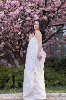 People, rest, comfort and leisure concept - young woman through the evening streets wrapped in a blanket. beautiful young girl in the park and a flowering tree sakura