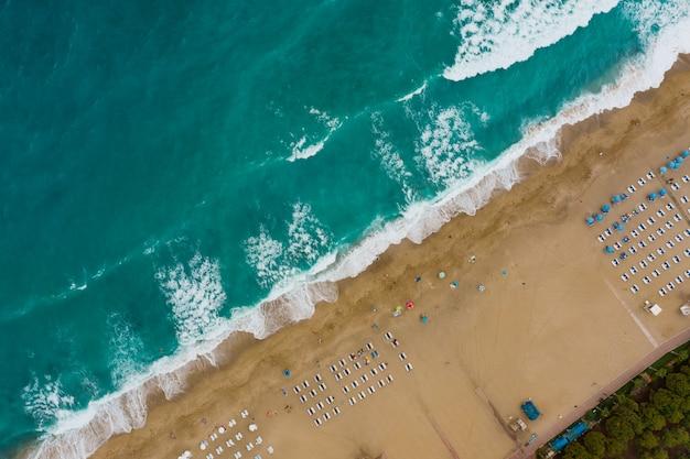 Люди, отдыхающие на пляже, наслаждаются летними каникулами