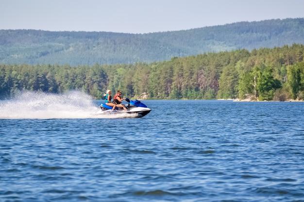 사람들은 더운 여름날 호수에서 스쿠터를 타고