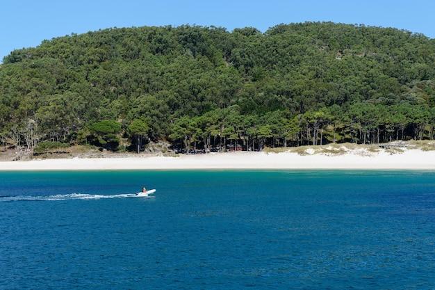Люди катаются на надувной моторной лодке по безлюдному песчаному берегу красивого природного ландшафта