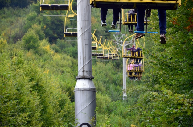 People ride on a cable car. the legs of passengers hang over the mountain forest