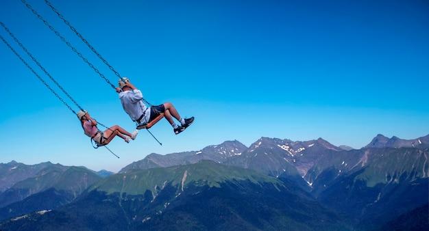 사람들은 절벽 위로 그네를 타고 산에서 익스트림 엔터테인먼트를 즐길 수 있습니다.