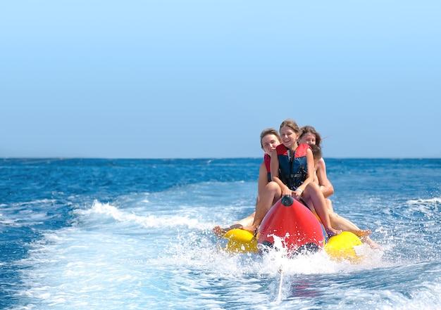 人々はバナナボートに乗ります。真っ青な海と澄んだ空。幸せな休暇。