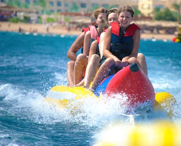 人々は晴れた夏の日にバナナボートに乗ります。真っ青な海と澄んだ空。