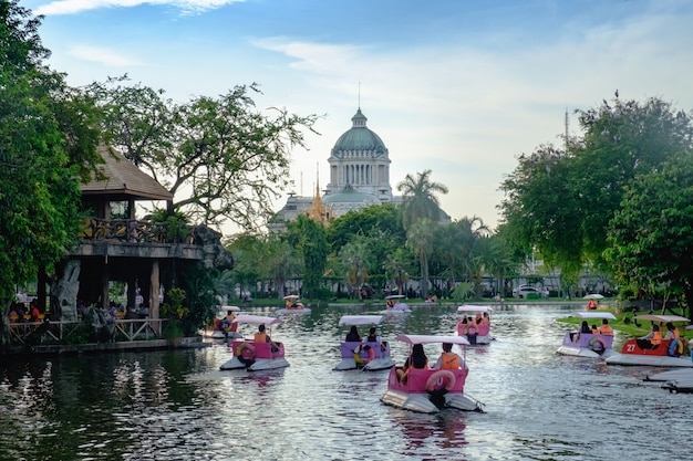 People ride pedal boats or water bicycle at lake with the ananda samakhom throne hall