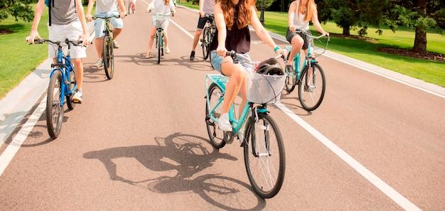 아스팔트 도로에 도시 공원에서 자전거를 타는 사람들. 건강한 생활 습관과 건강 관리. 도로에서 함께 즐거운 시간을 보내는 다섯 사람의 모습을 잘라냅니다. 밖에 서 아름 다운 화창한 날
