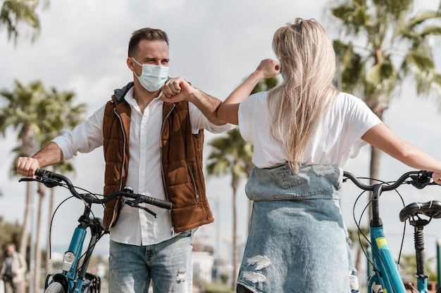 Persone in sella a una bicicletta mentre indossano una maschera medica