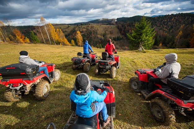 People riding a off-road vehicles on hill