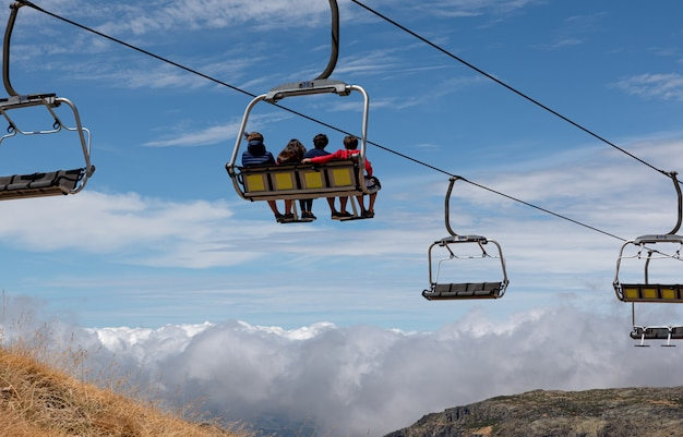 People riding ski station chairlifts, watching the mountains and the horizon, back