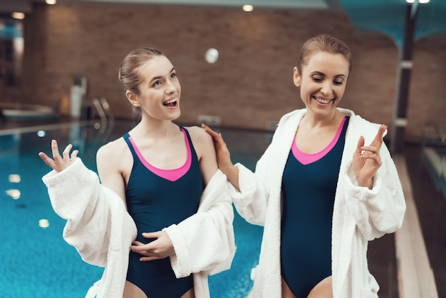 People in robes and swimsuits standing near pool