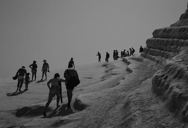 People on a rocky surface near a beach