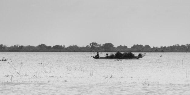 People rowing boat in tonle sap lake, kampong phluk, siem reap, cambodia