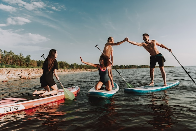 People rowing surfs in sea with paddles.