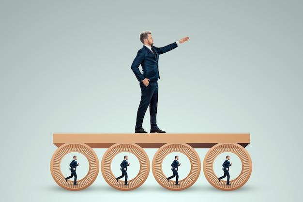 사람들은 상사를 위해 일하는 햄스터 휠에서 뛰고 있습니다. 사무, 노예 제도, 삶, 사업, 조작, 통제로부터의 해방의 개념.