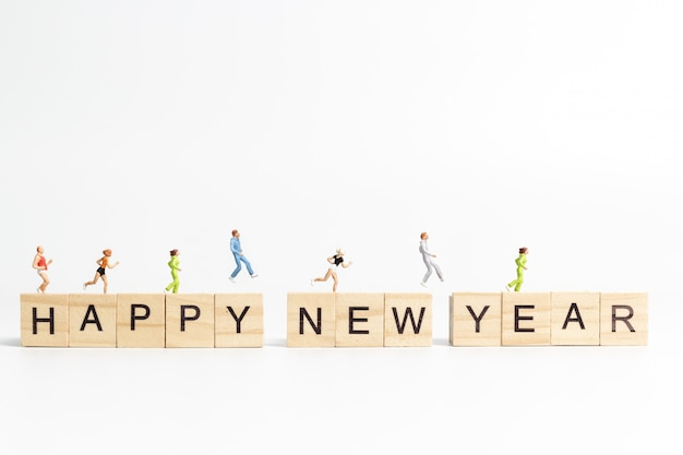 People running on happy new year lettering wooden block