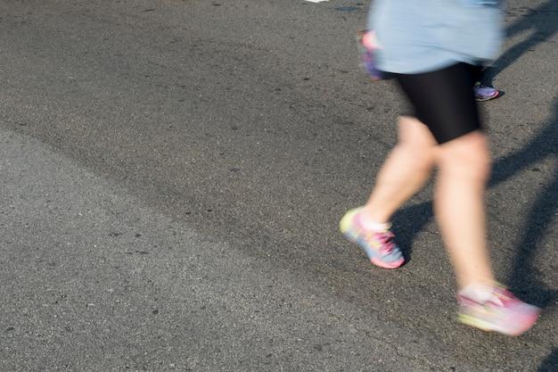 Люди, участвующие в уличных гонках по асфальту, с эффектом размытия движения
