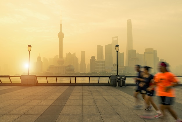 People running in morning at yangtze river with shanghai downtown in background in shanghai, china.