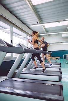 フィットネスセンターでのトレーニングセッションでトレッドミルの上を走っている人