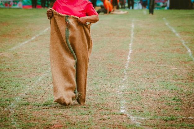 田舎の文化の分野で袋レースを実行している人々